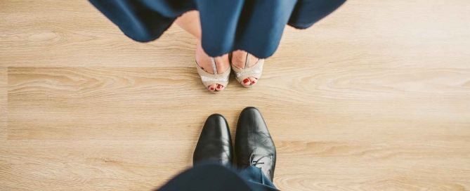 alimony couple standing on wood floor facing each other wearing blue suit and dress